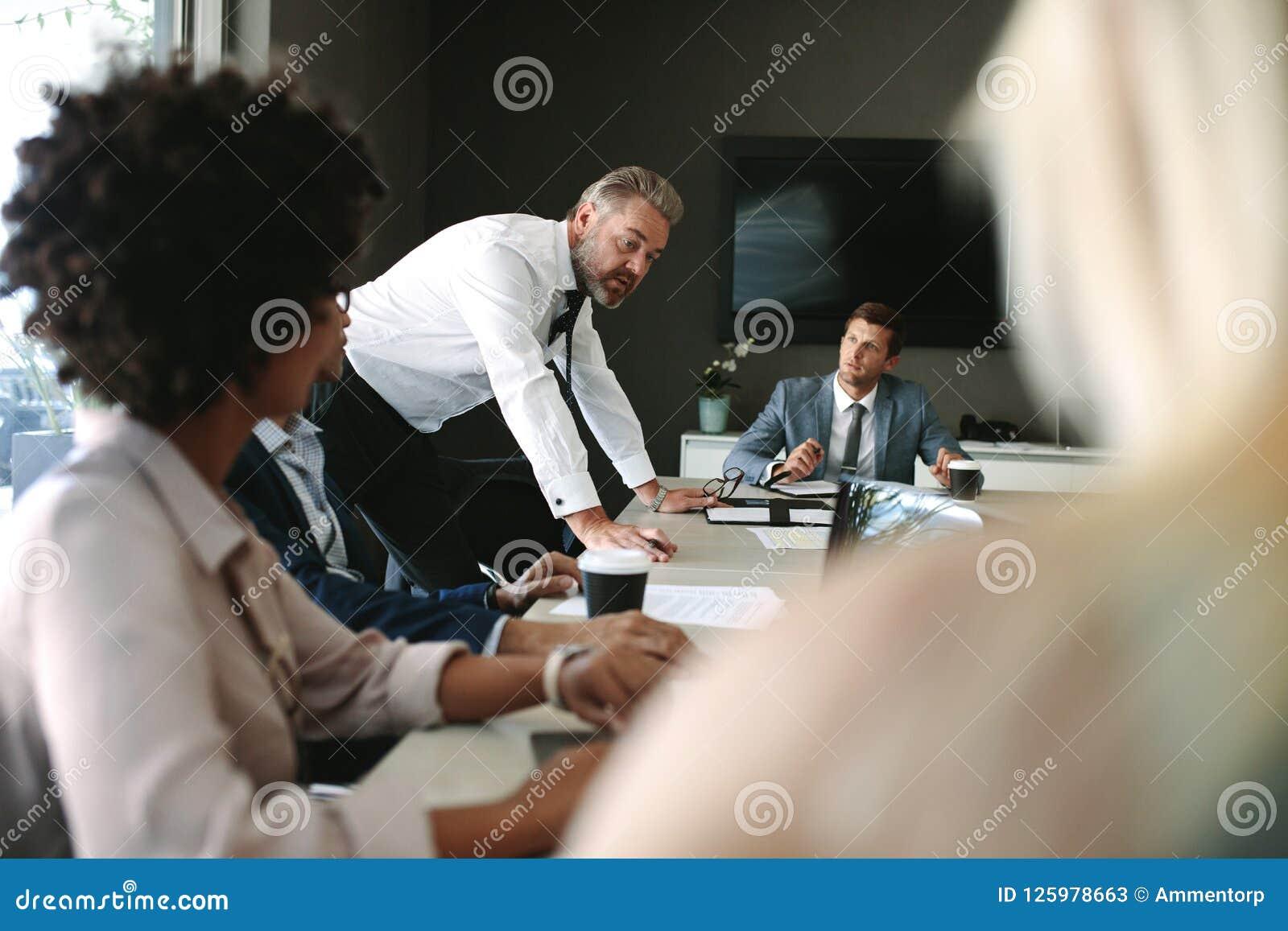 Dirigente anziano che spiega qualcosa al suo gruppo in una riunione