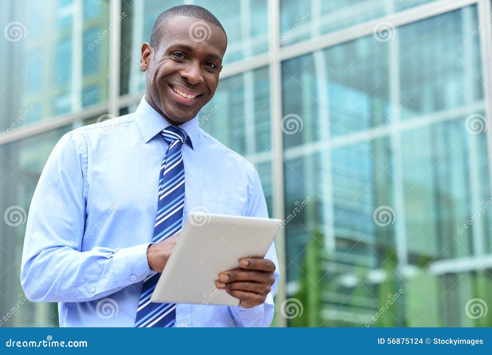 Dirigente maschio felice che posa alla macchina fotografica