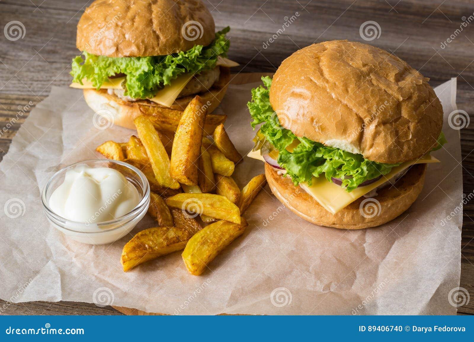 Dirija o Hamburger feito com galinha, cebola, pepino, alface e queijo na tabela de madeira com fritadas da batata