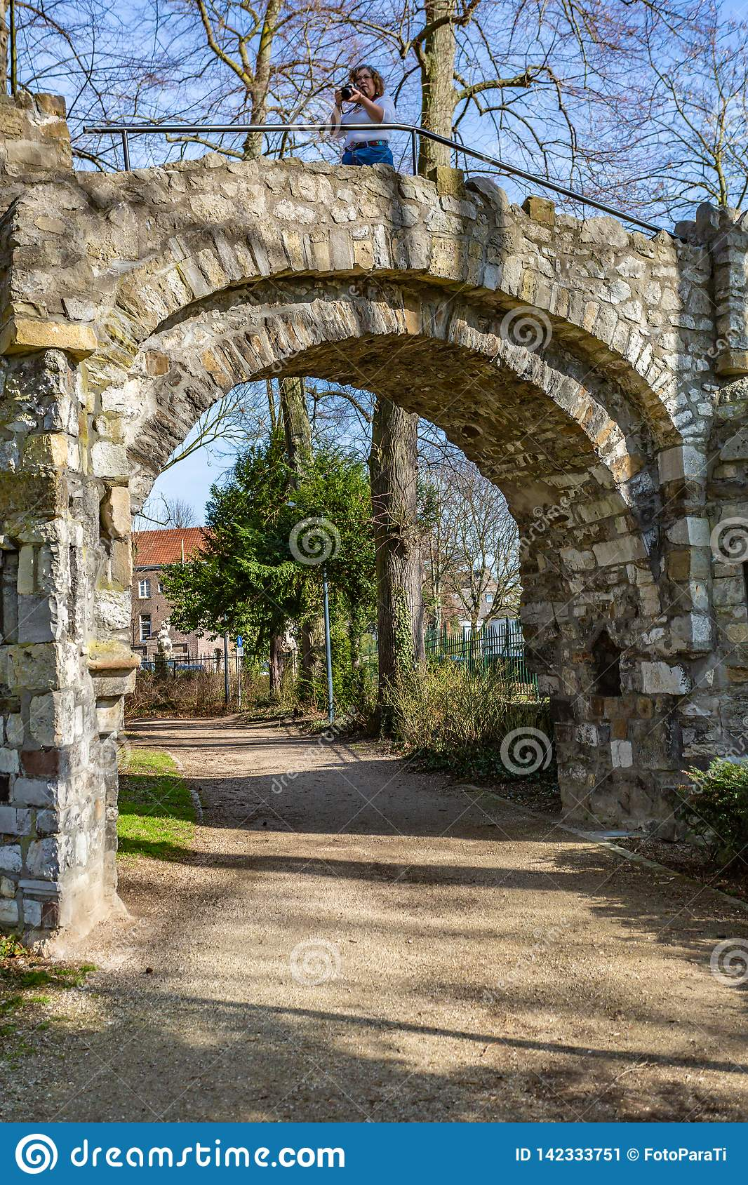 Dirt road and the arch of an old stone bridge with a woman in it taking a picture,