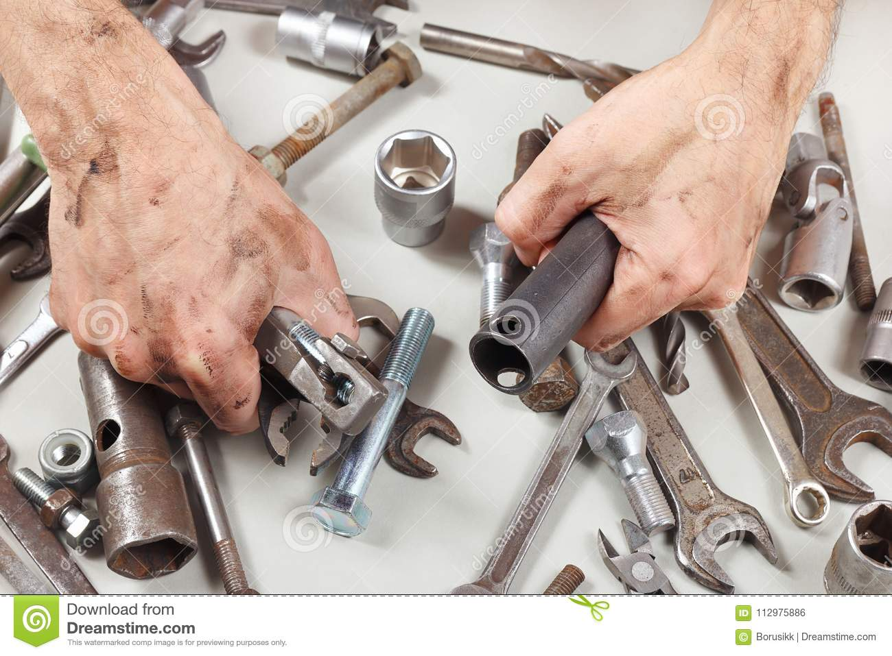 Dirty hand of master with tools for repairing machines in workshop