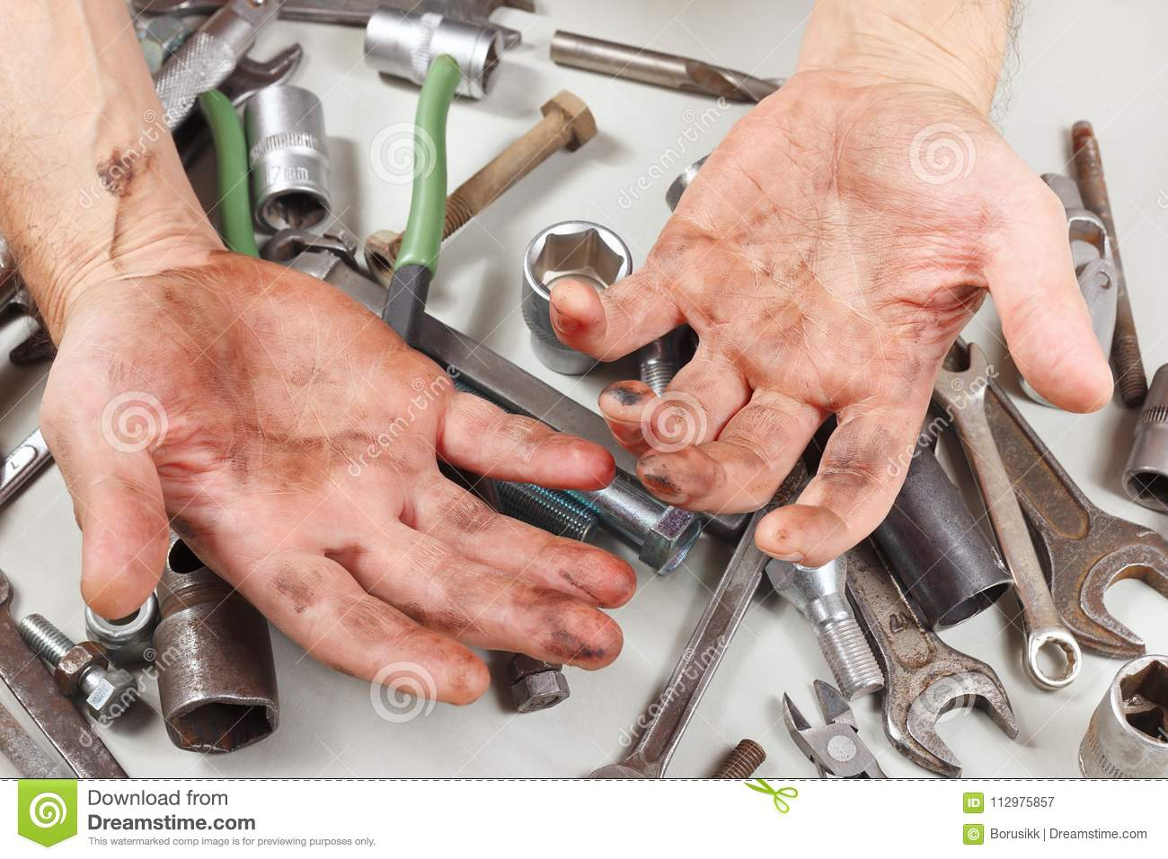 Dirty hand of serviceman behind his work in workshop