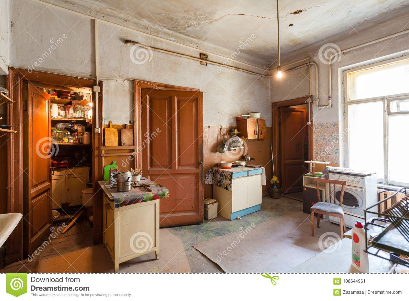 Dirty Kitchen With Furniture And Gas Stoves Is In The Apartment For ...