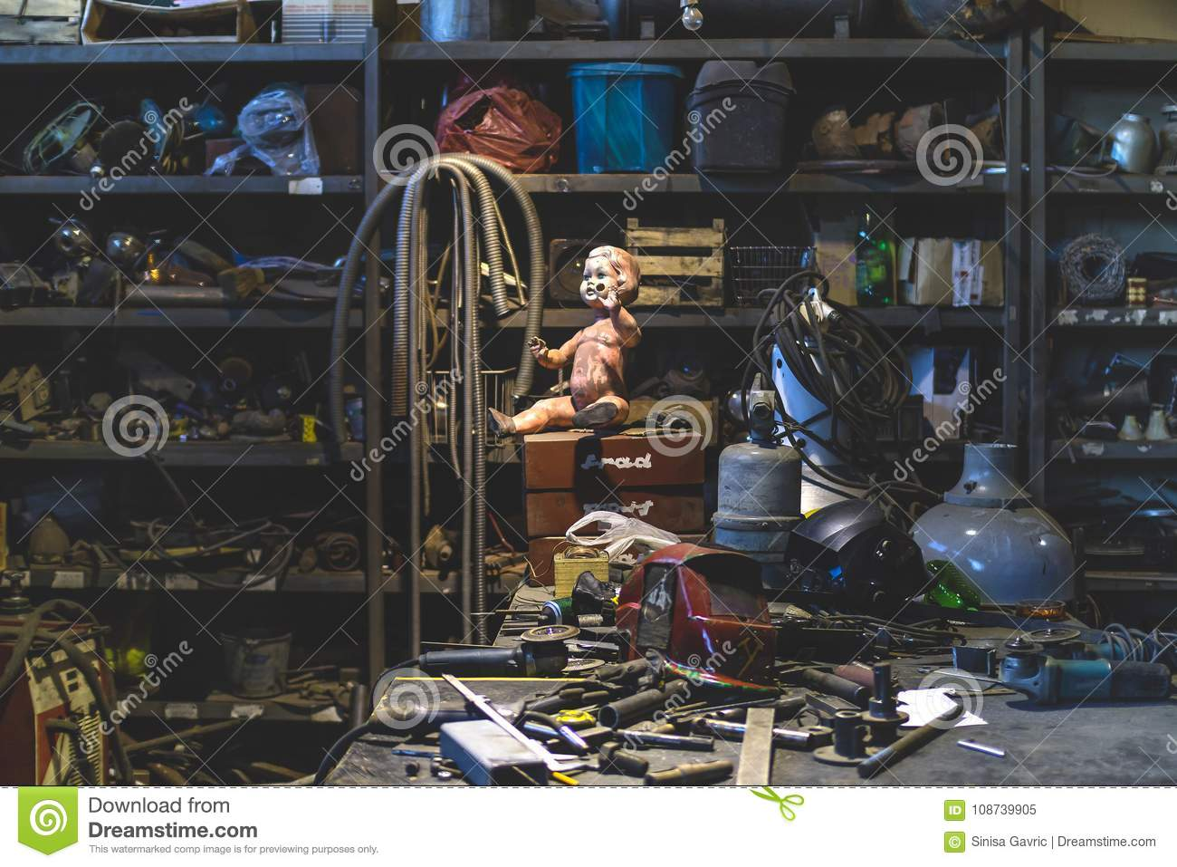 Dirty plastic baby doll posing inside of a metal shop