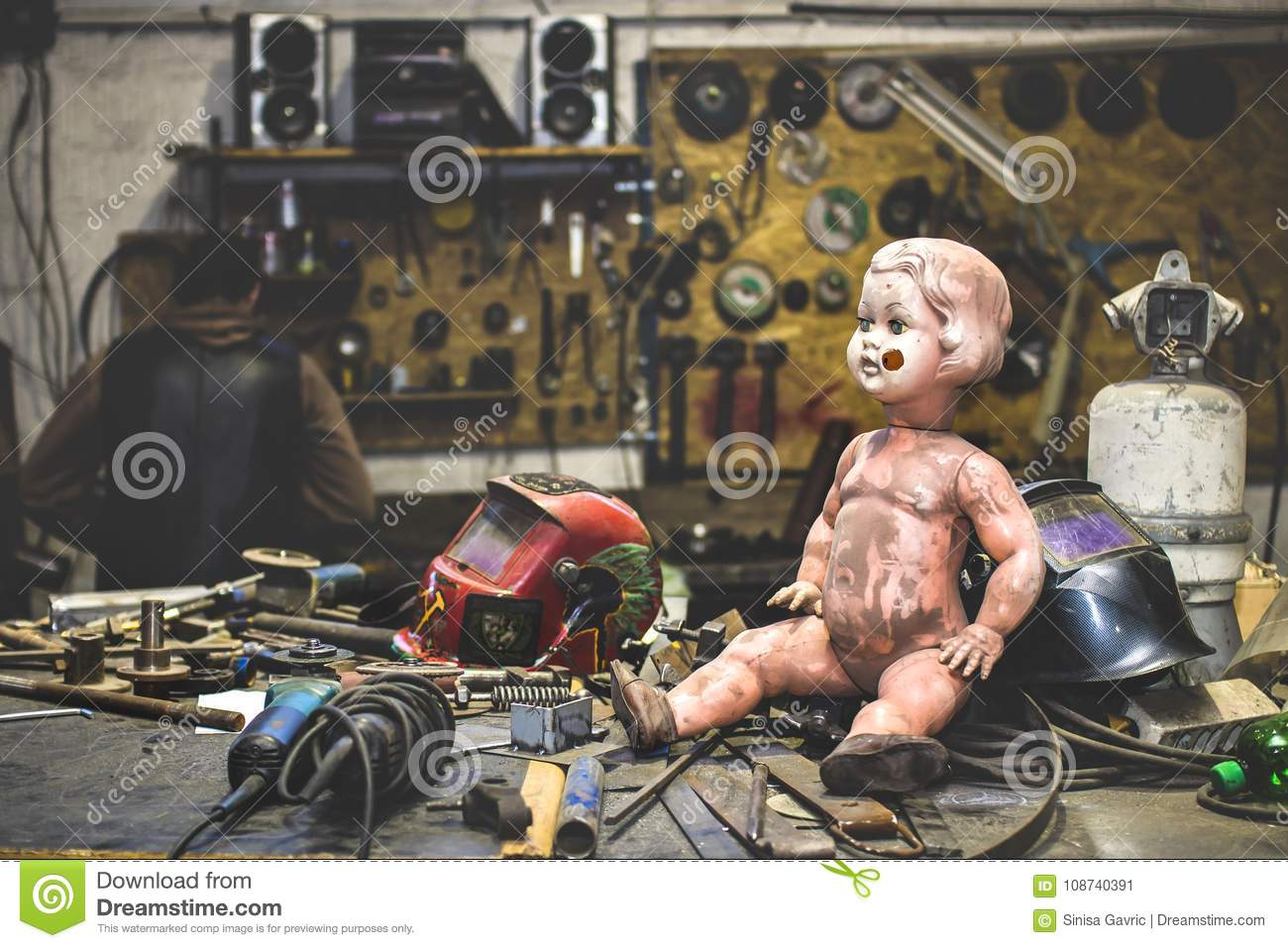 Dirty plastic baby doll posing inside of a metal work shop