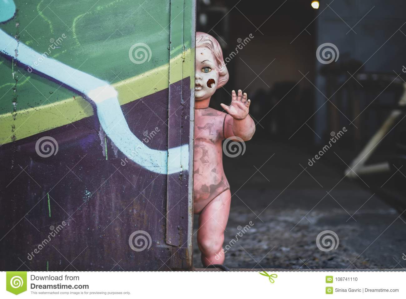 Dirty plastic naked baby doll standing by the door at the metal shop looking eerie and hunted weaving