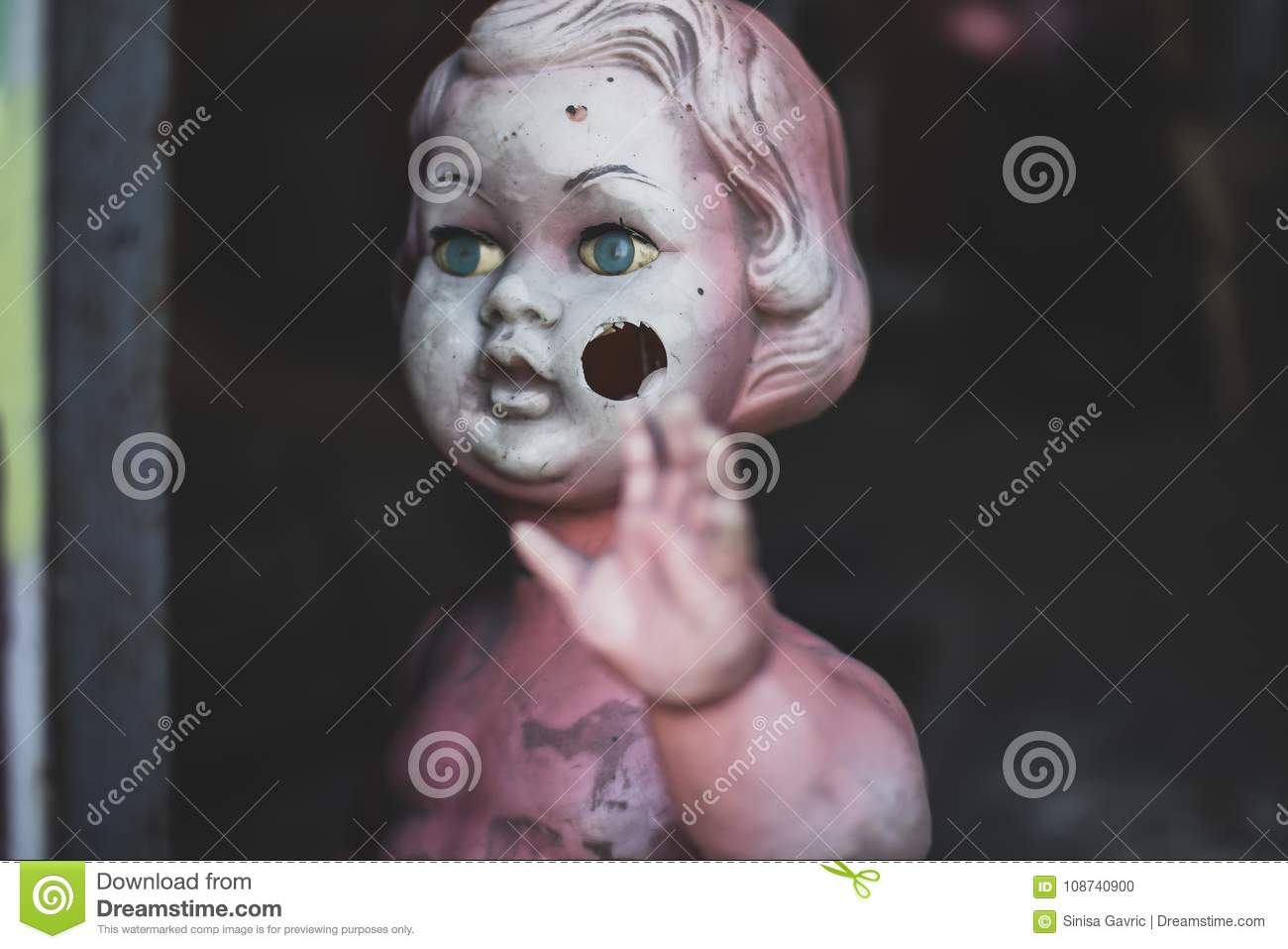 Dirty plastic naked baby doll standing by the door at the metal shop looking eerie and hunted weaving closeup