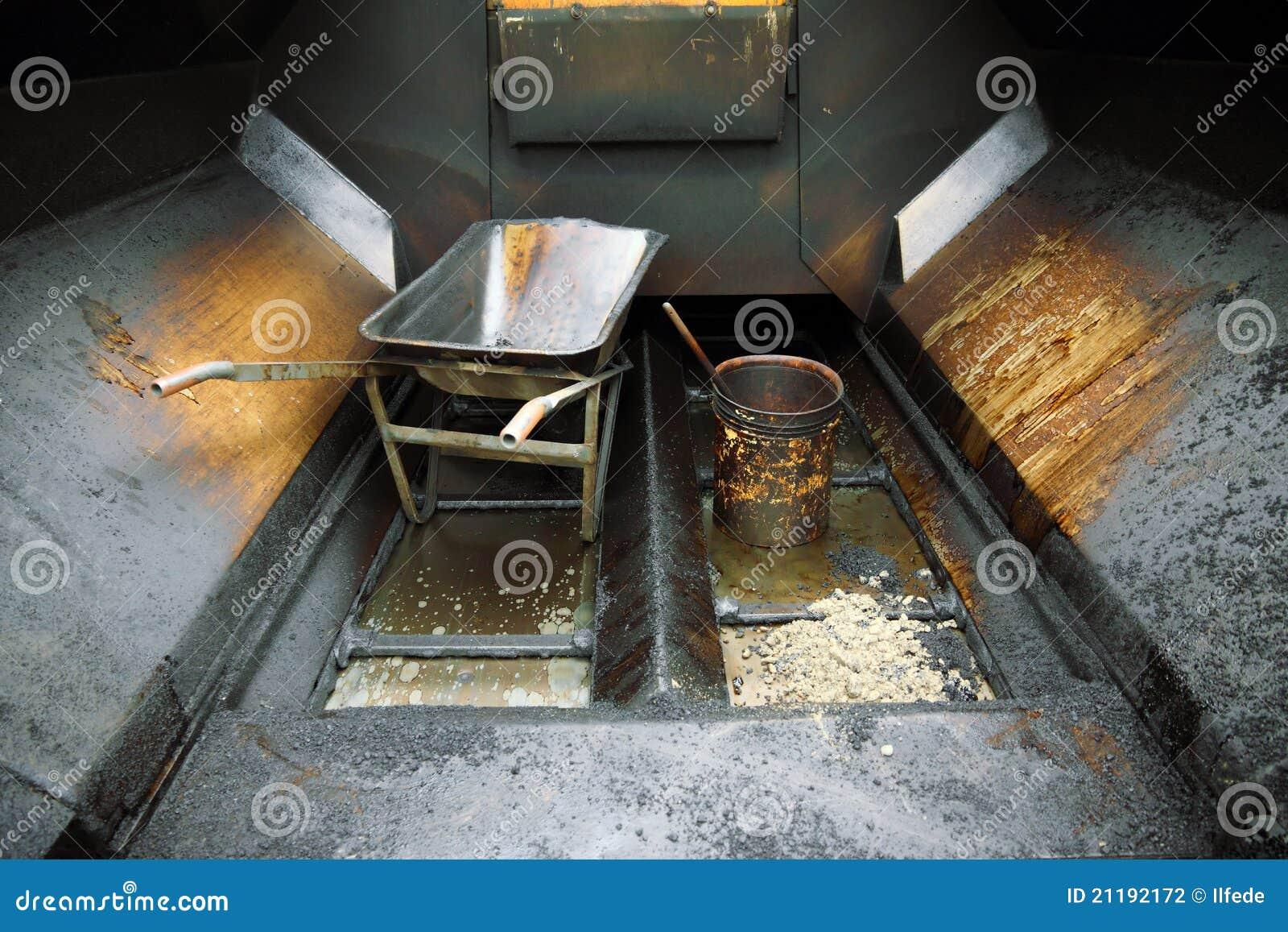 Dirty tar bucket and wheelbarrow