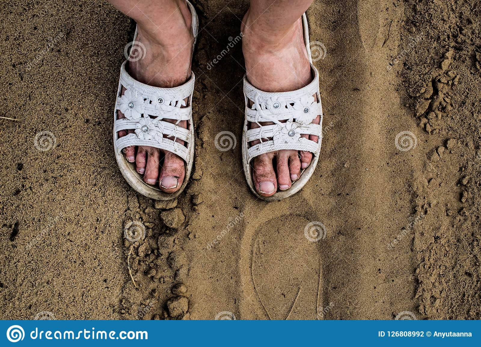 Dirty, working and tired girl`s feet in white dusty Slippers on the background of sand.