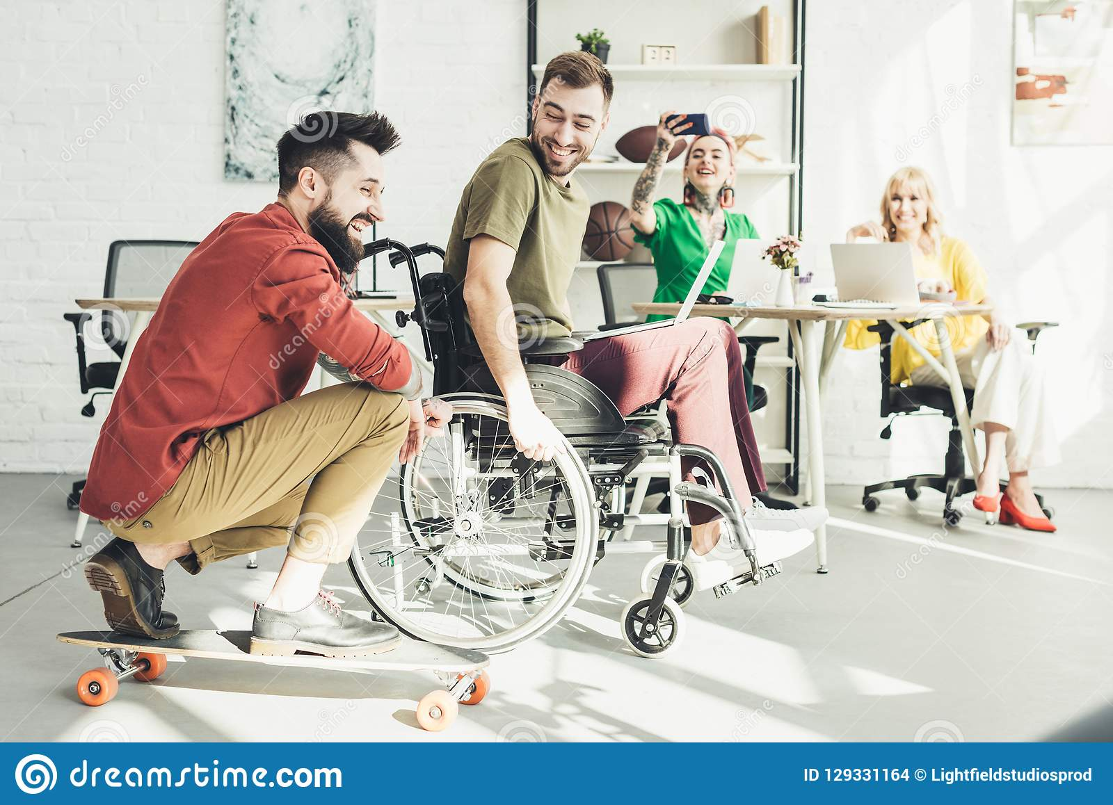 Disabled businessman with laptop with colleague on skateboard and businesswomen behind in office stock images
