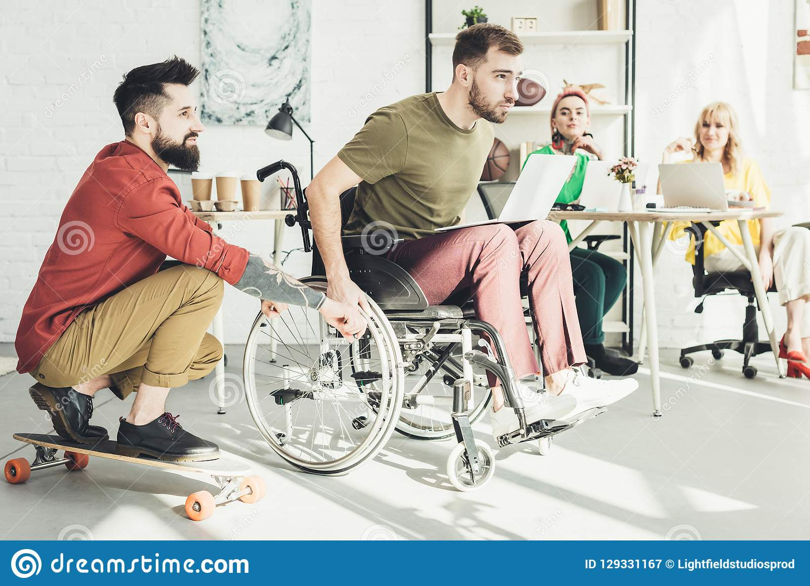 Disabled businessman with laptop with colleague on skateboard and businesswomen behind in office royalty free stock photography