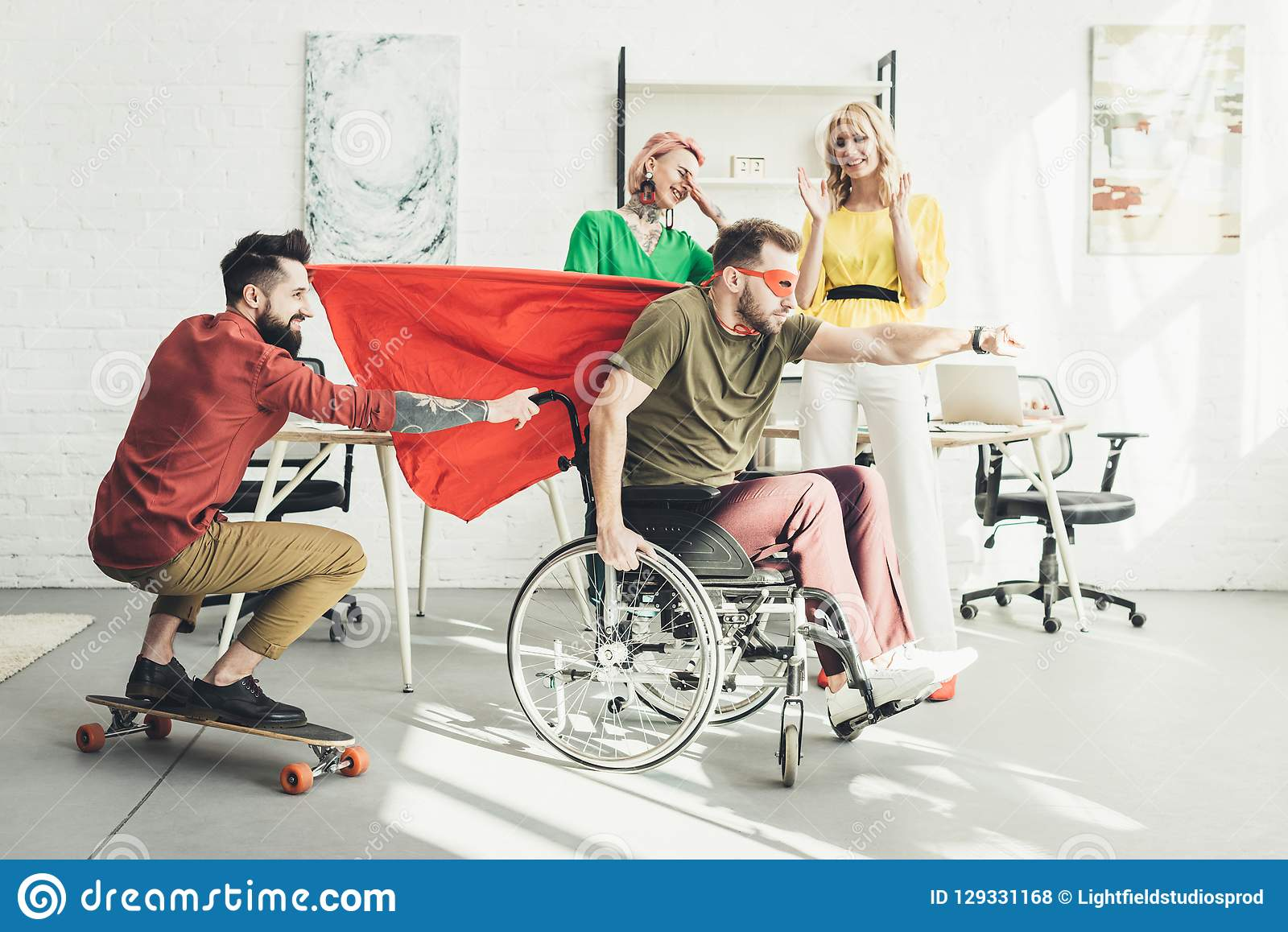 Disabled businessman in superhero costume with colleague on skateboard and businesswomen behind in office royalty free stock photos