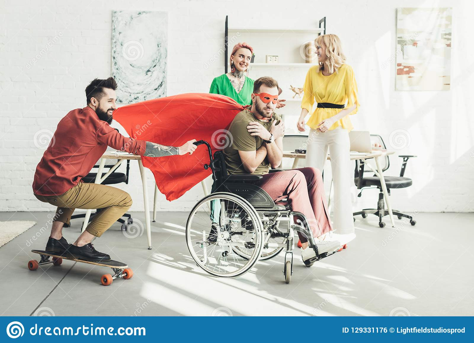 Disabled businessman in superhero costume with colleague on skateboard and businesswomen behind in office royalty free stock image