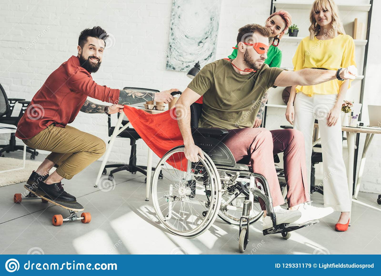 Disabled businessman in superhero costume with colleague on skateboard and businesswomen behind in office royalty free stock images
