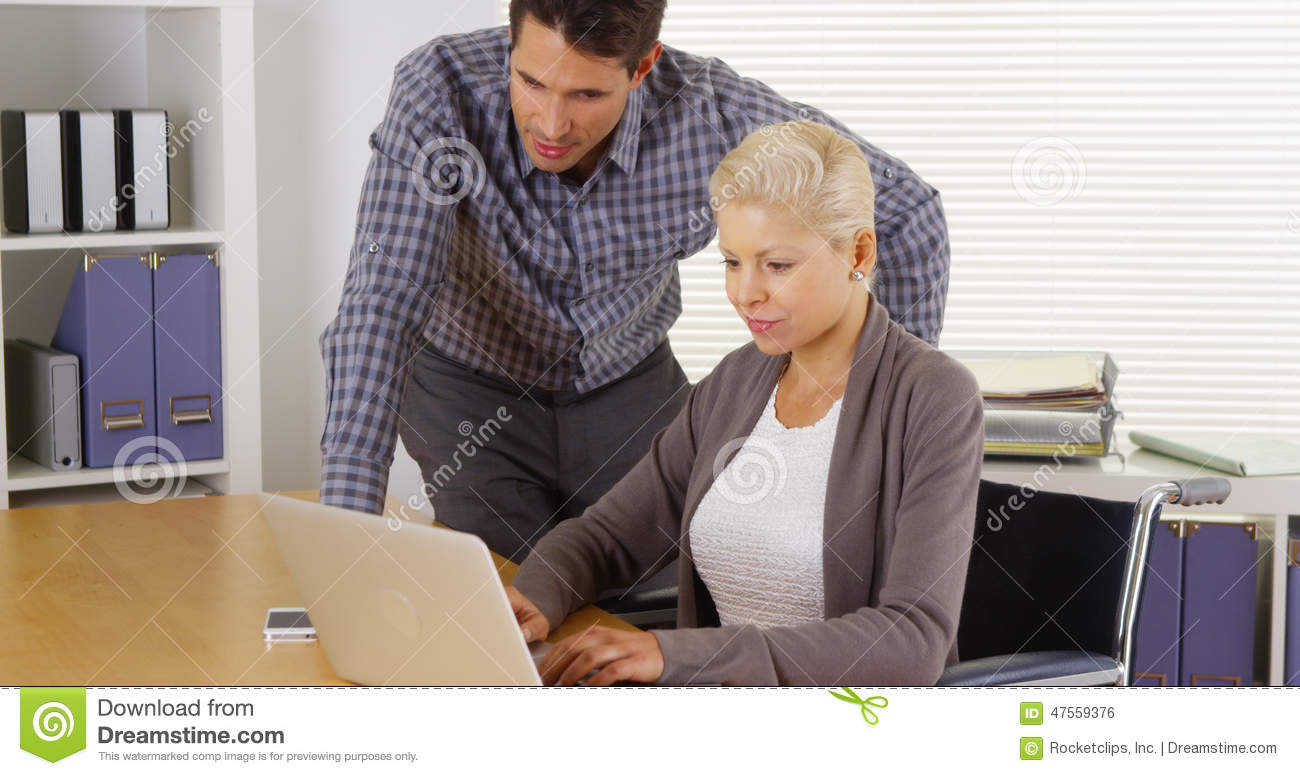Disabled businesswoman and coworker working together on laptop
