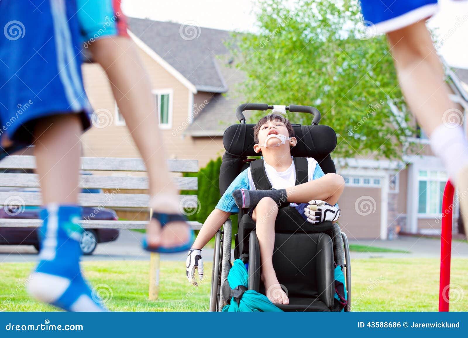Disabled little boy in wheelchair watching children play