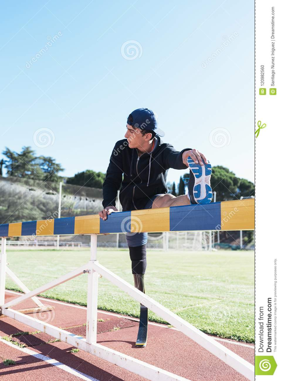 Disabled man athlete stretching with leg prosthesis. Paralympic Sport Concept.