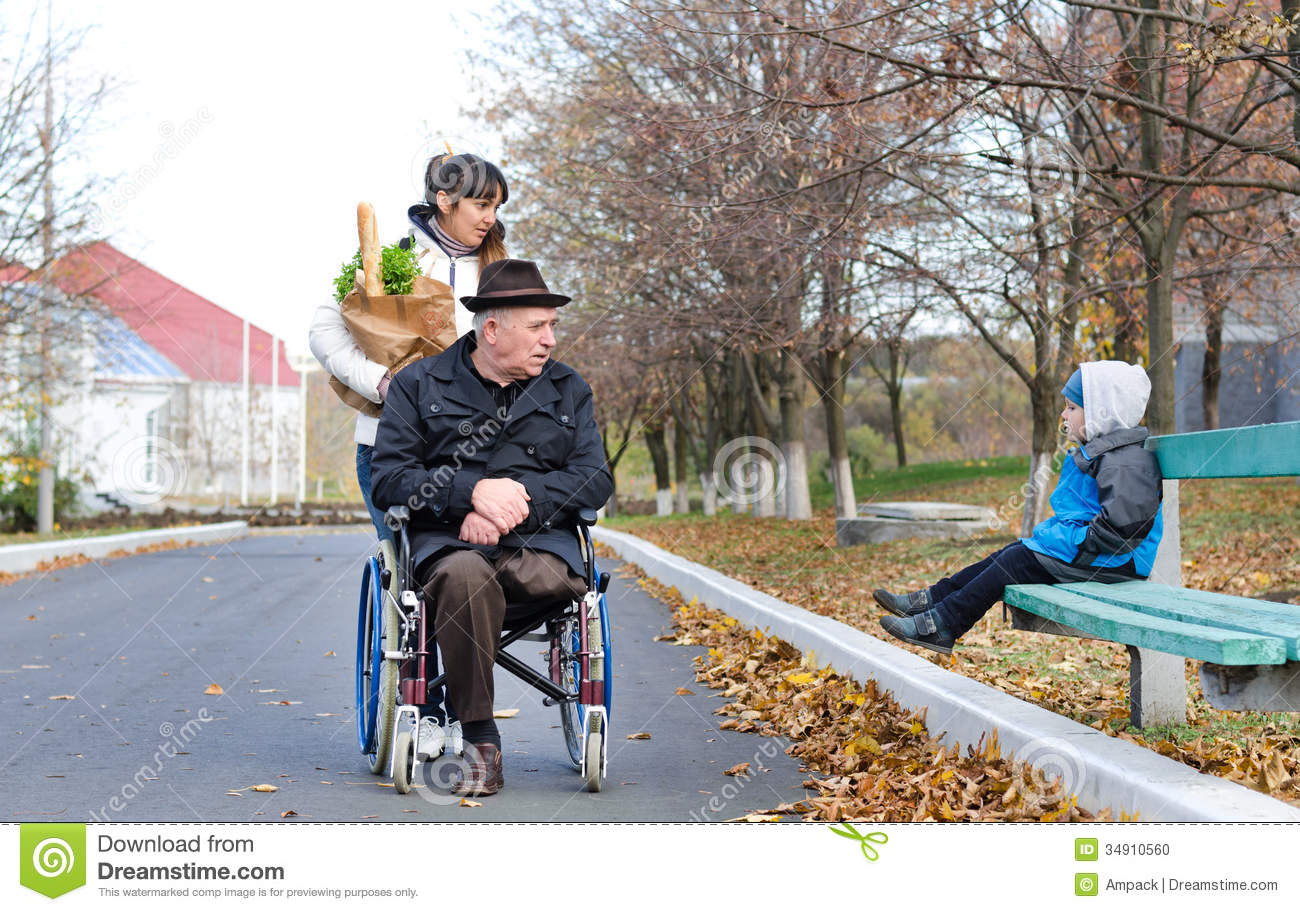 Disabled Man And His Carer Chat To A Little Boy Stock Photo - Image: 34910560