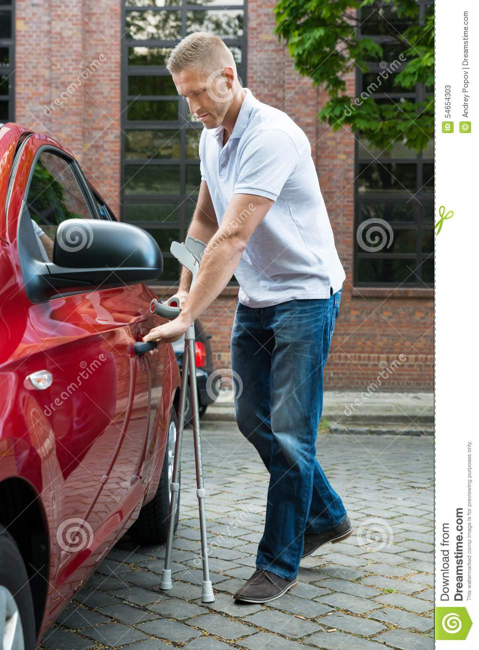 Disabled man holding crutches opening door of a car
