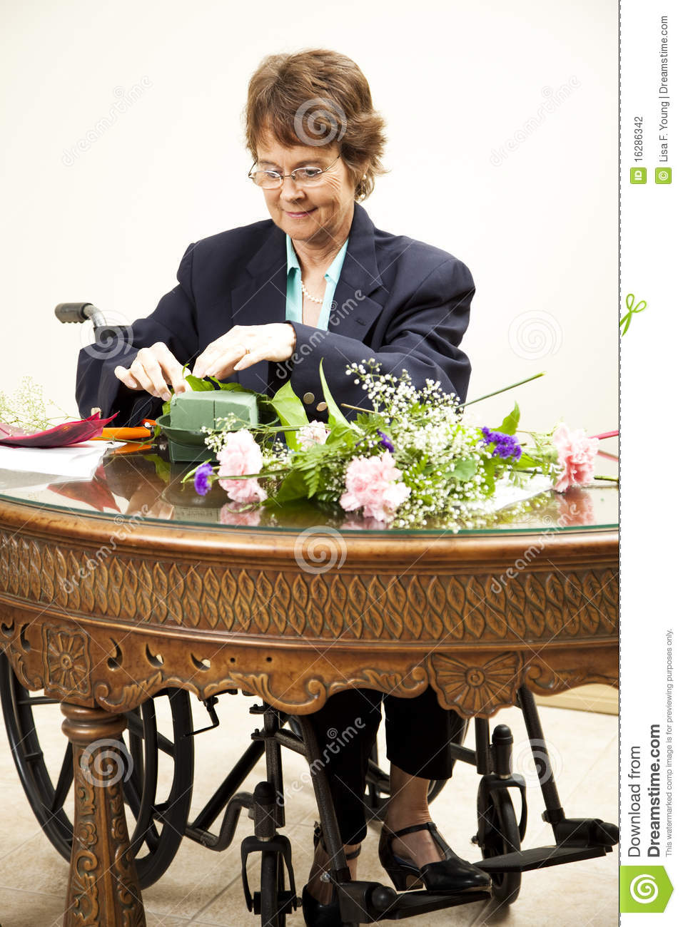 Mature woman in wheelchair making a flower arrangement.