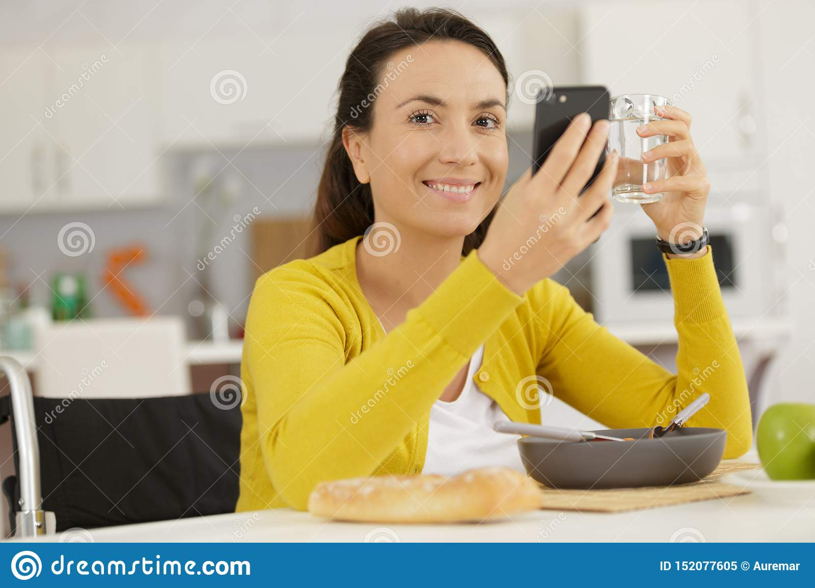 Disabled woman using phone and holding glass water