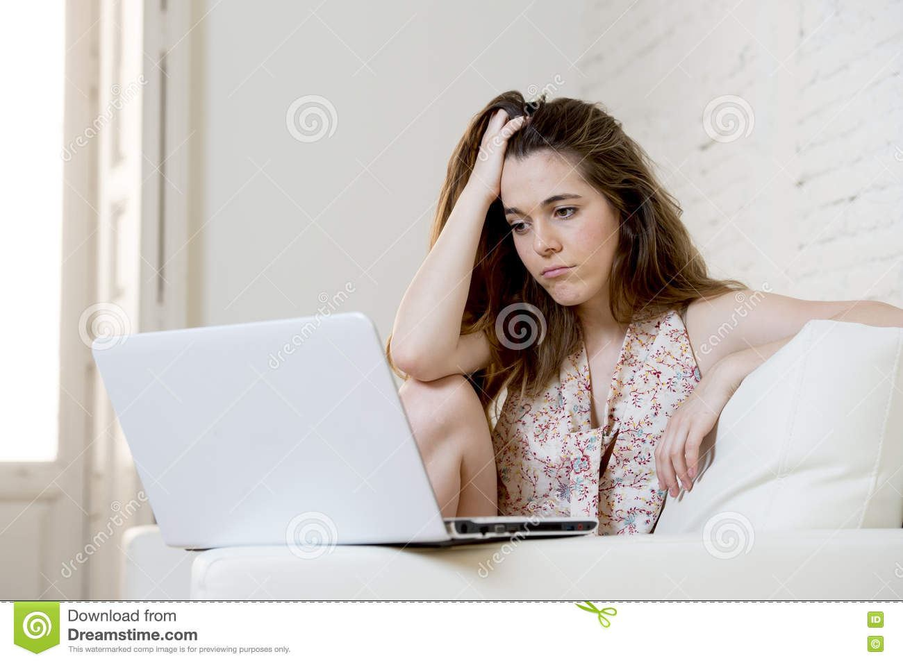 Disappointed girl at home couch using internet for studying with laptop computer