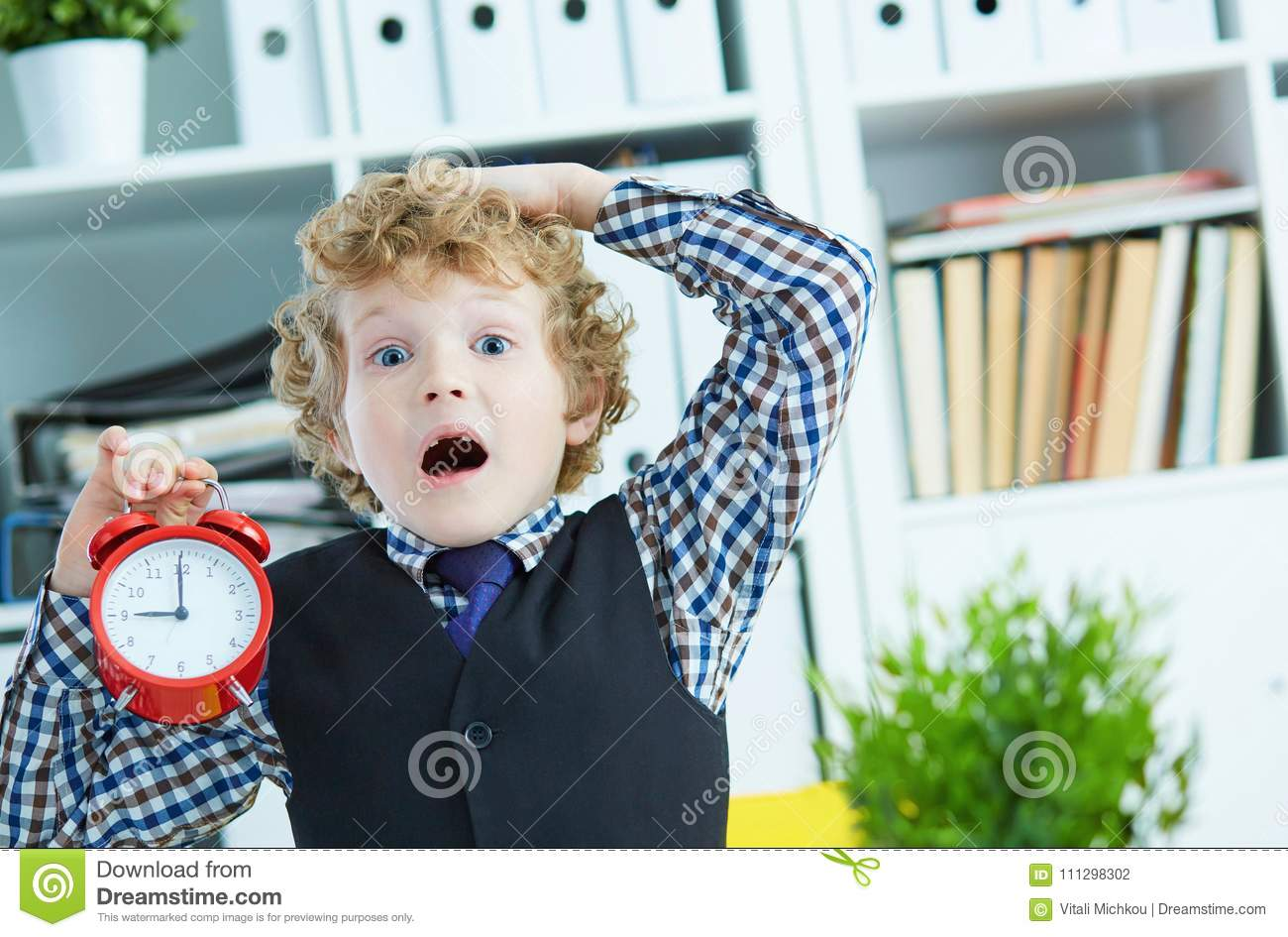 Disappointed kid boss holding a big red alarm clock in his hand suggesting you are late for work.
