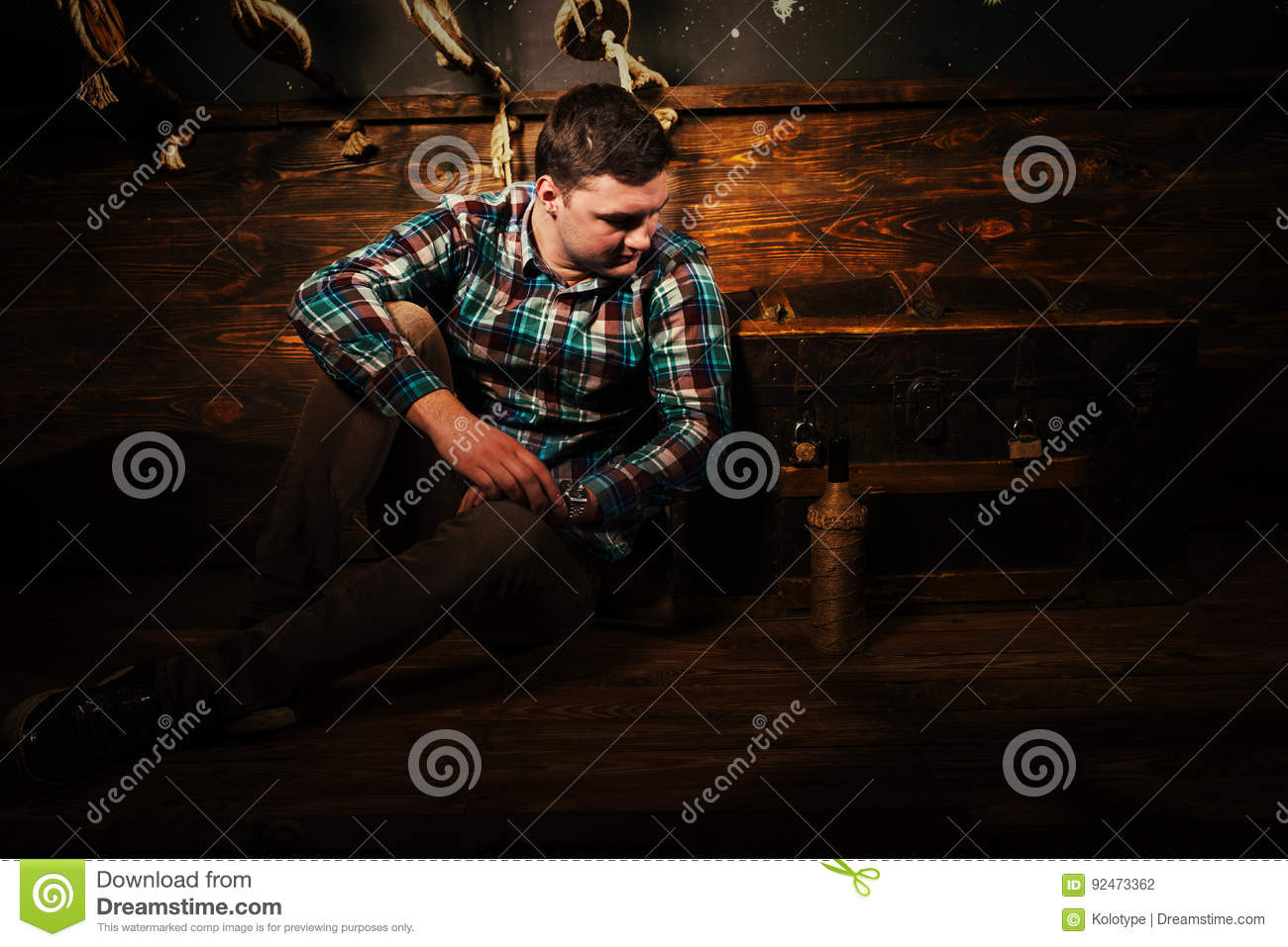 Disappointed man sits near a chest, holding glass bottle and try