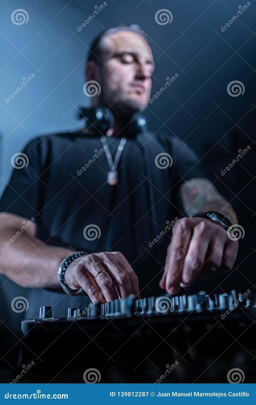 Discjockey som spelar hus- och technomusik i en nattklubb Blanda och kontrollera musiken