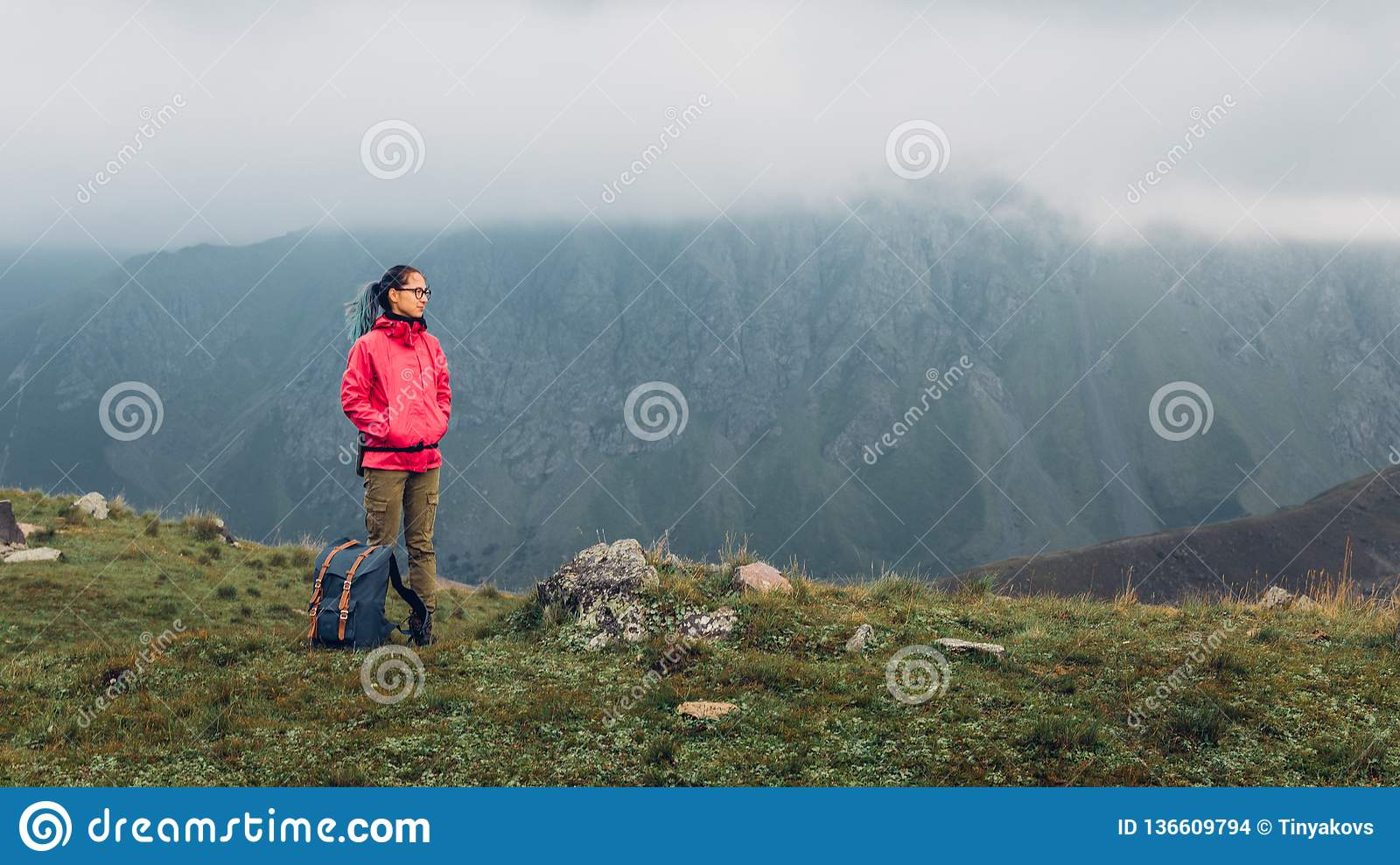 Discovery Travel Destination Adventure Concept. Young Hiker Woman With Backpack Rises To The Mountain Top with Copy Space