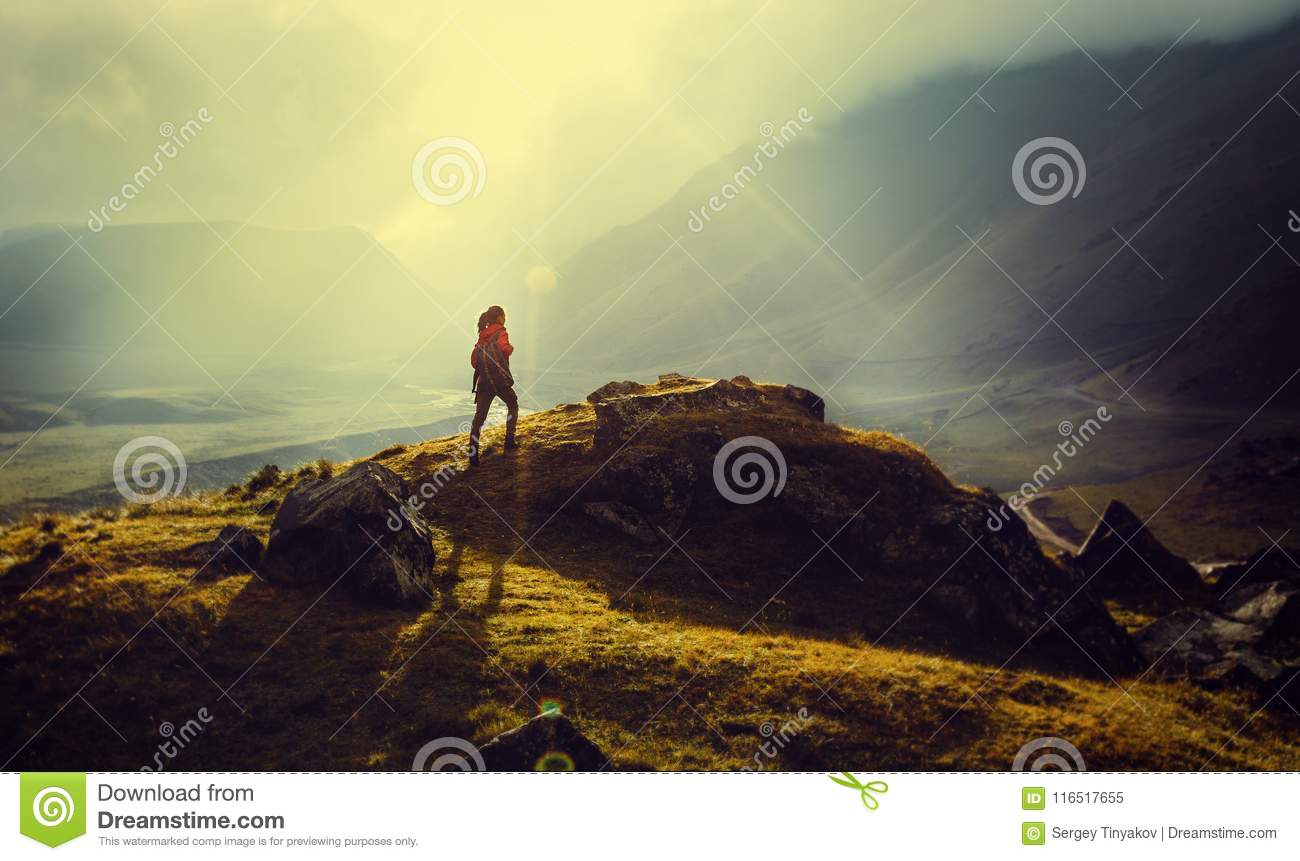 Discovery Travel Destination Concept. Hiker Woman With Backpack Rises To The Mountain Top Against Backdrop Of Sunset Vintage Toned