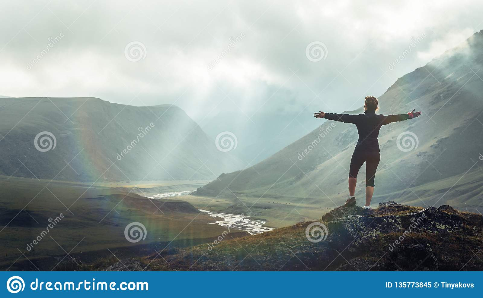 Discovery Travel Destination Concept. Hiker Young Woman With Backpack Rises To The Mountain Top Against Backdrop Of Sunset, Rear