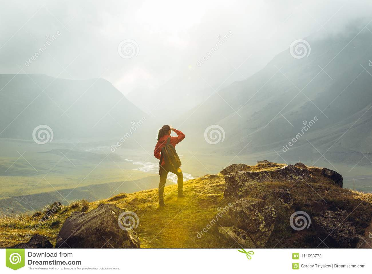 Discovery Travel Destination Concept. Hiker Young Woman With Backpack Rises To The Mountain Top Against Backdrop Of Sunset, Rear V