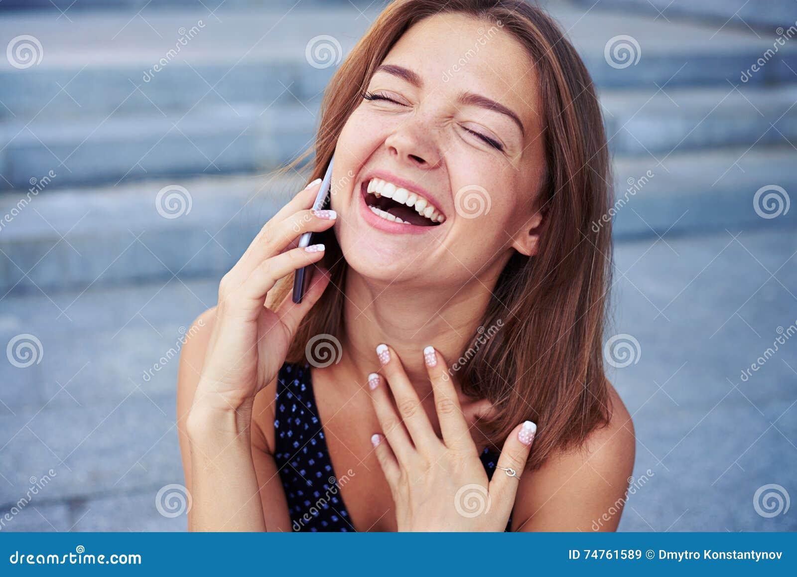Discurso fêmea atrativo no telefone e riso sinceramente