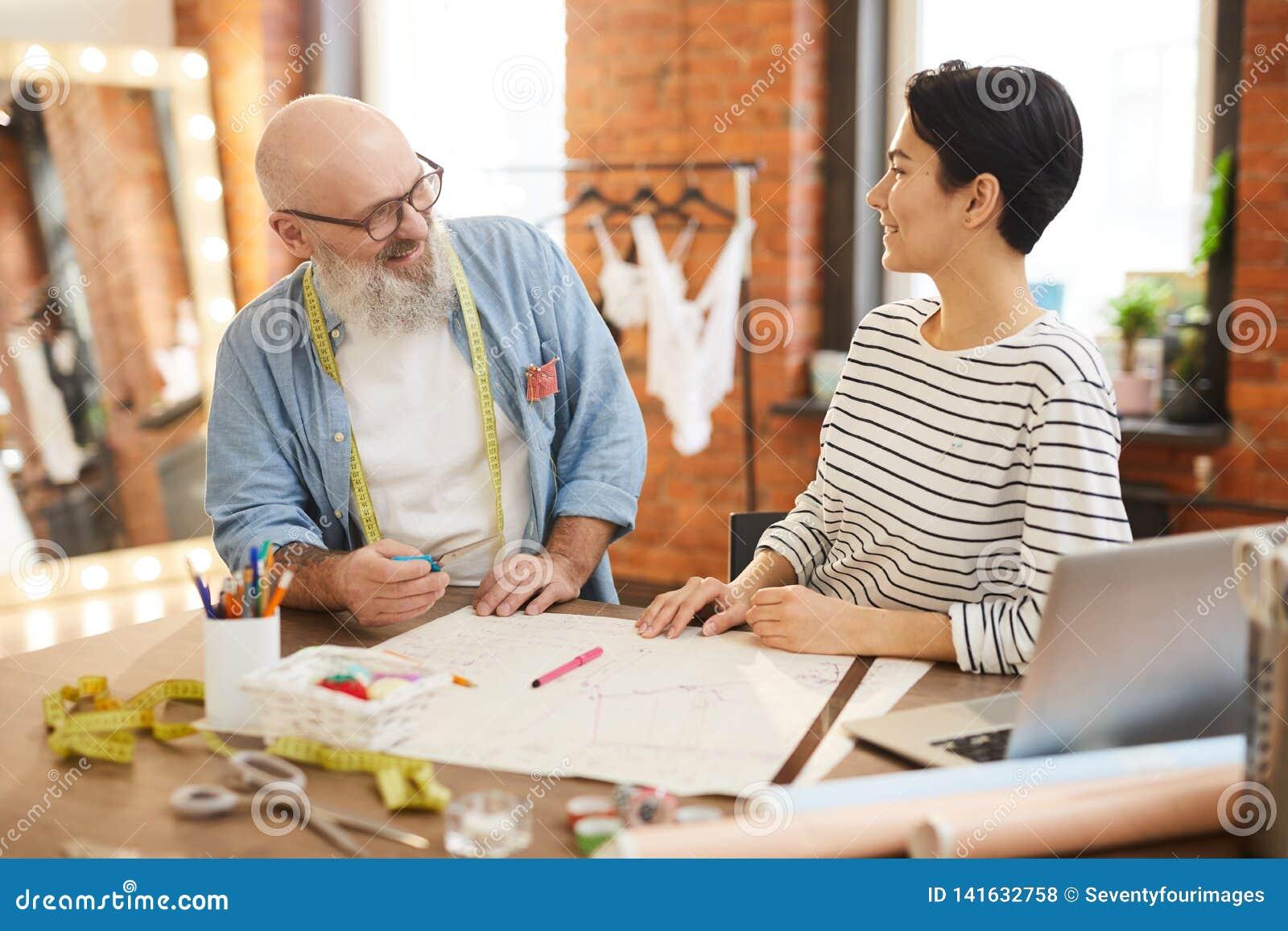 bd792999f9 Hombres maduros y mujeres jovenes en el casualwear que tiene discusión de  la nueva colección de la moda por el escritorio en la adaptación de la  tienda