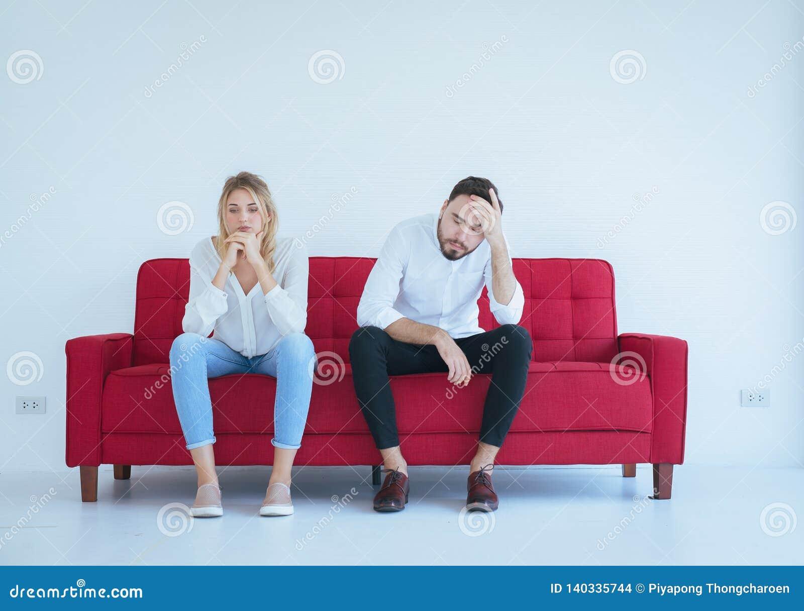 A discussão do marido com conflito da esposa e pares furando no sofá vermelho, emoções negativas, copia o espaço para o texto, fu