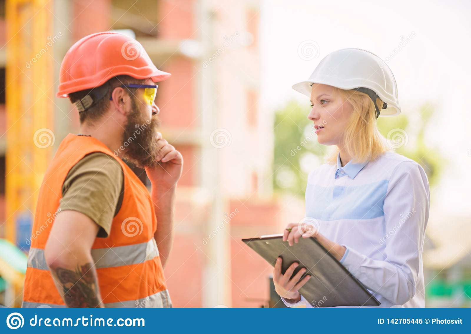 Discuss progress project. Construction project inspecting. Safety inspector concept. Woman inspector and bearded brutal