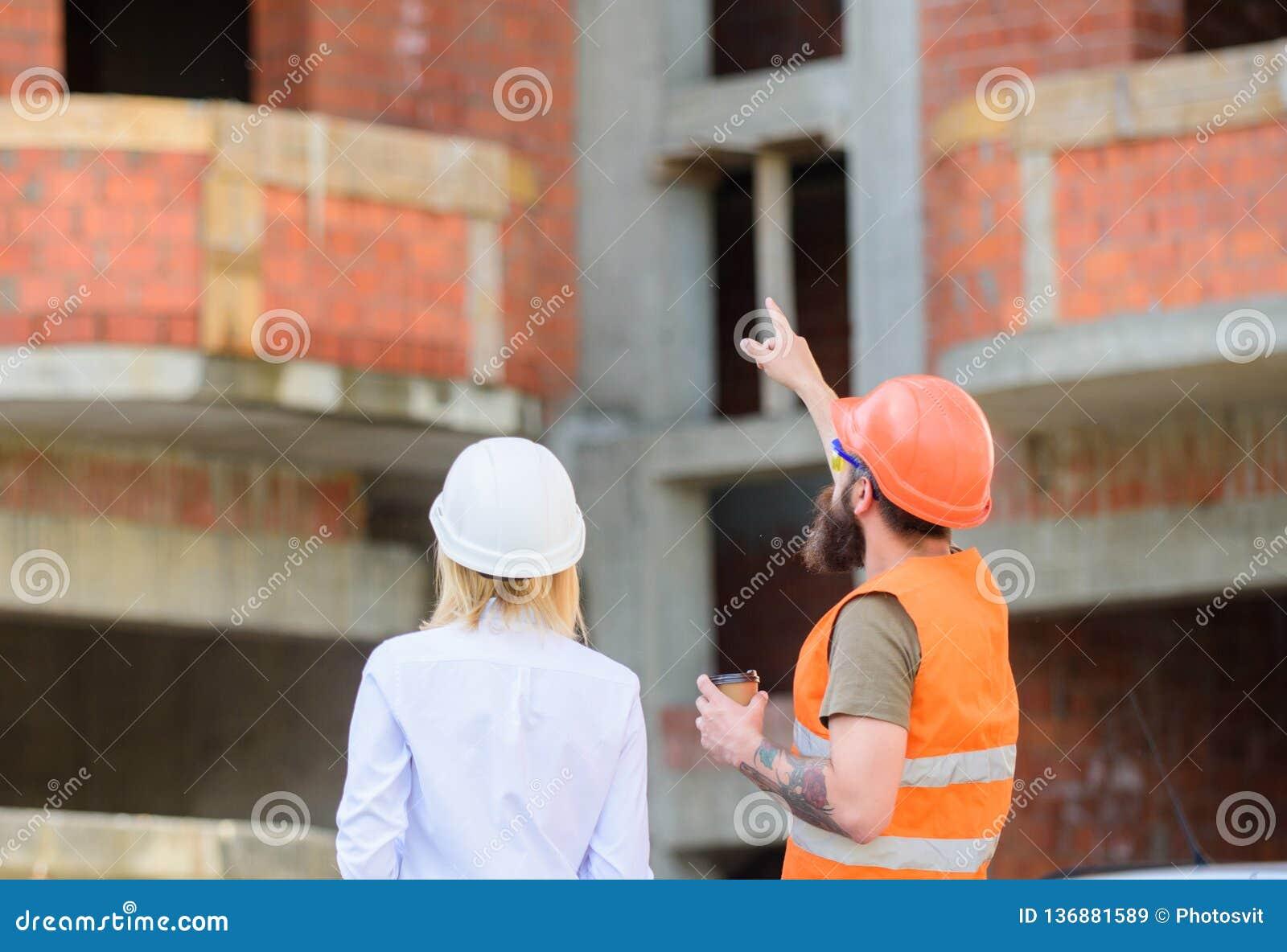 Discuter le plan L ingénieur et le constructeur de femme communiquent au chantier de construction Relations entre les clients de