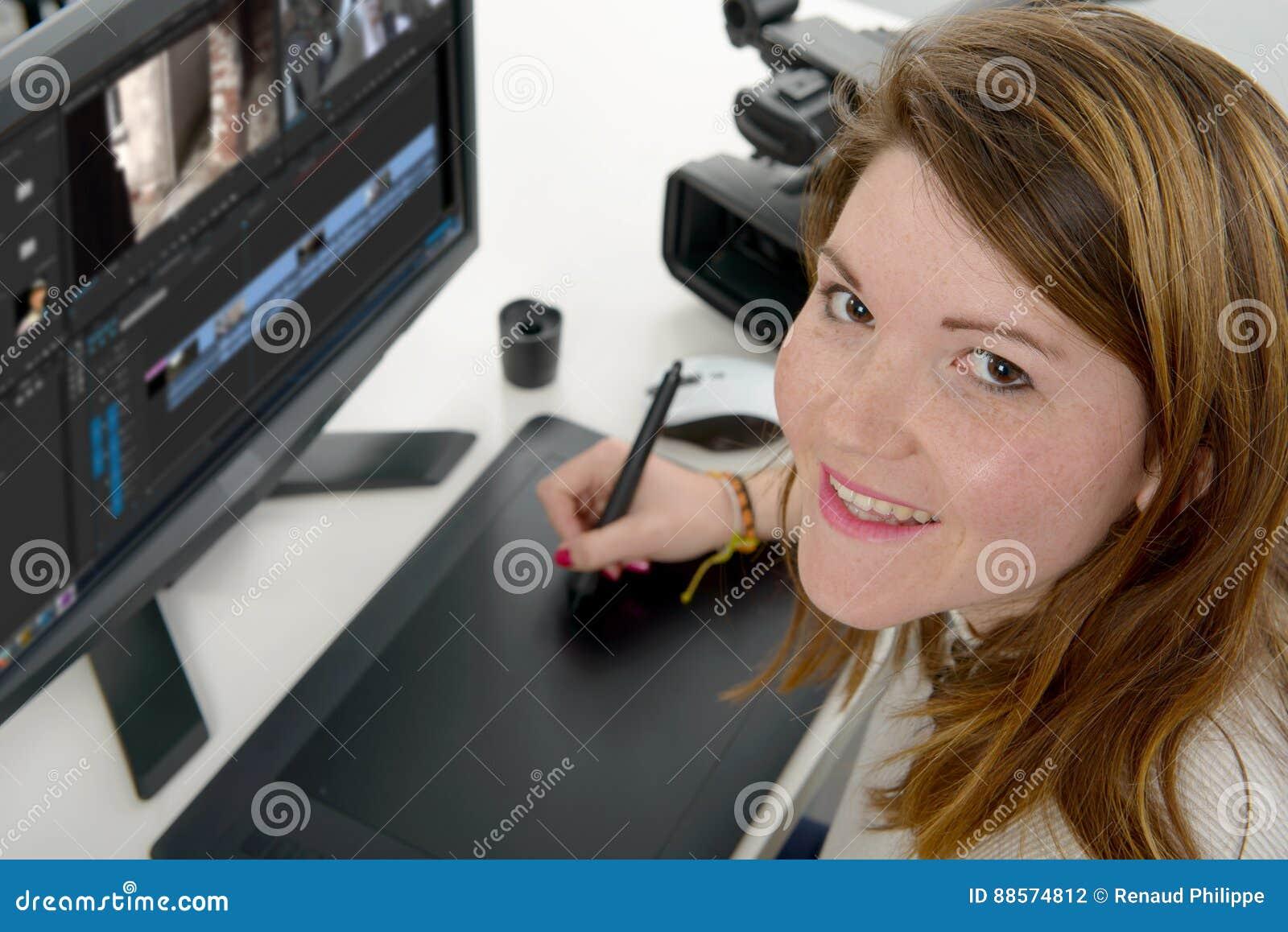 Diseñador de la mujer joven que usa la tableta de gráficos