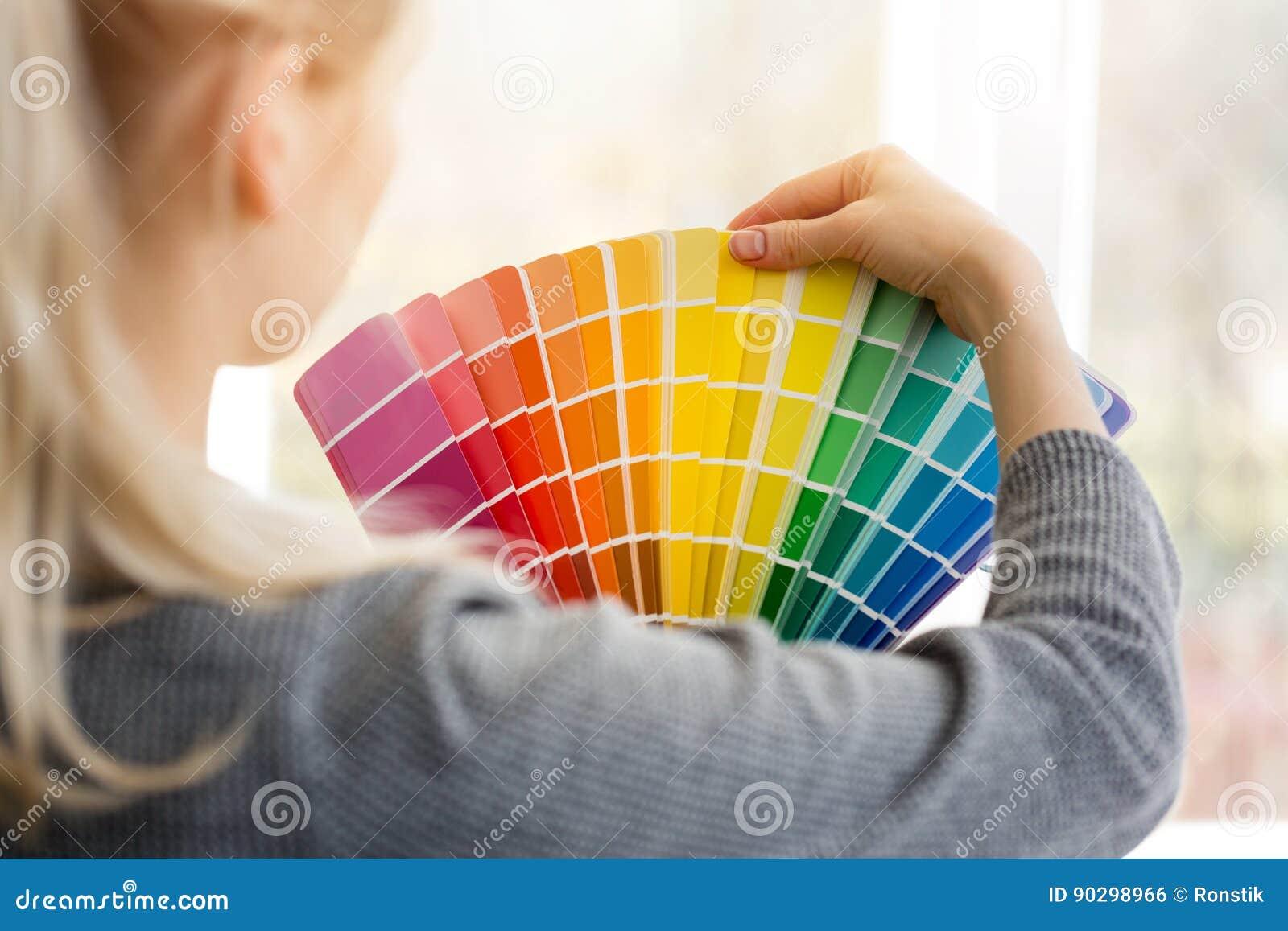 Diseñador de la mujer que elige color del diseño de palett de la muestra