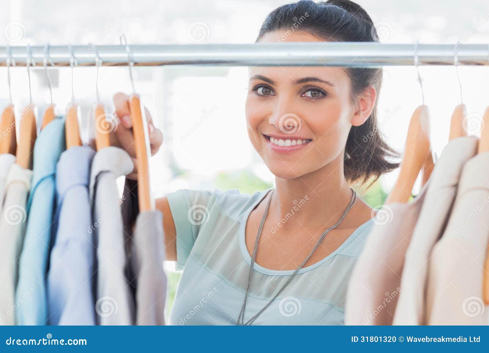 Dise ador de moda sonriente que mira la ropa foto de - Disenador de fotos ...