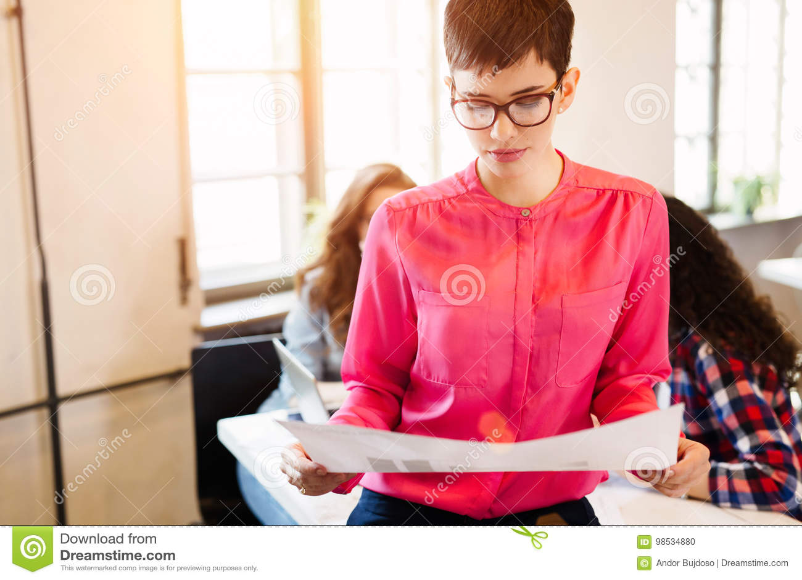 Diseñador de sexo femenino atractivo joven que mira esquema del proyecto