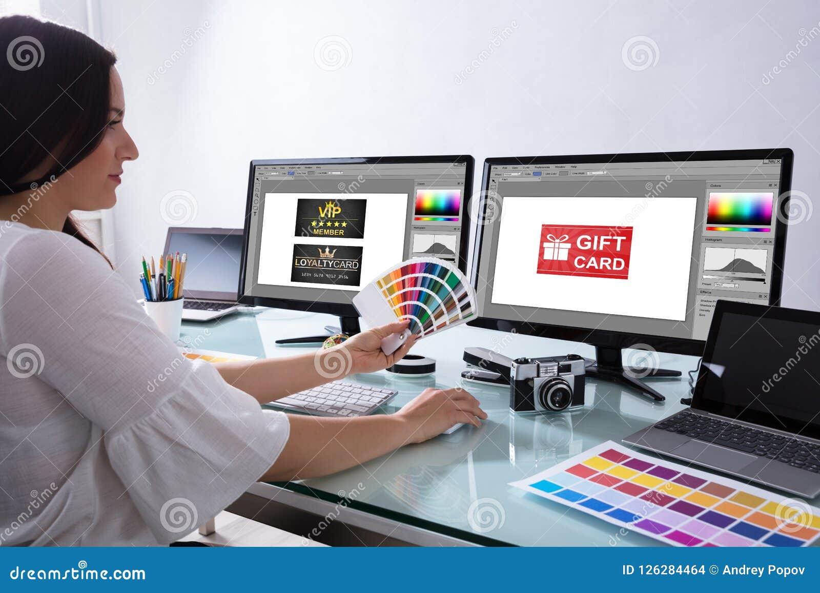 Diseñador de sexo femenino Holding Color Swatch que trabaja en oficina