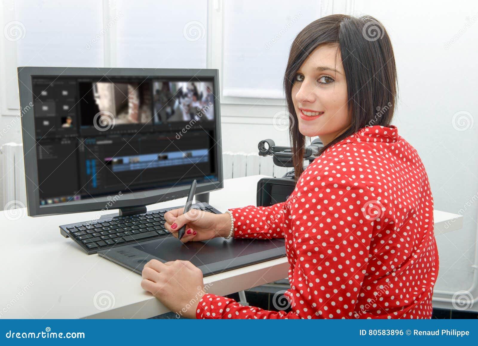 Diseñador de sexo femenino joven que usa la tableta de gráficos para corregir video