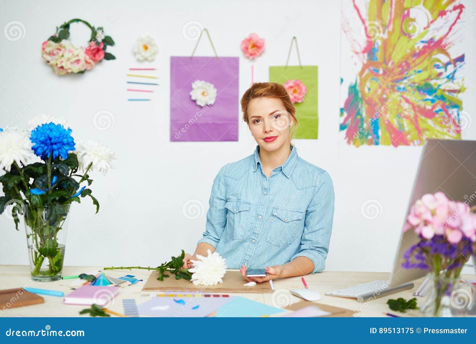 Diseñador floral confiado en el escritorio sucio