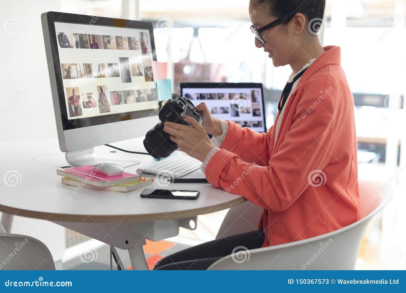 Diseñador gráfico de sexo femenino que mira las fotos en cámara digital el escritorio en una oficina moderna