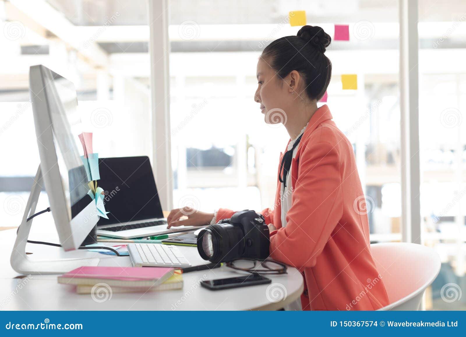 Diseñador gráfico de sexo femenino que trabaja en el ordenador portátil en el escritorio en una oficina moderna
