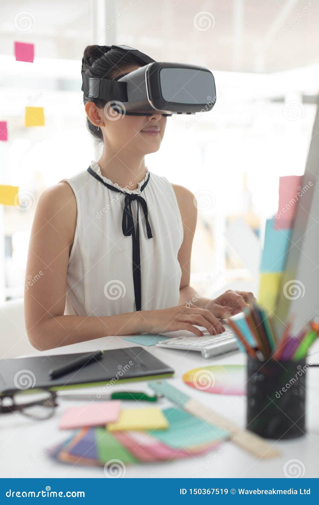 Diseñador gráfico de sexo femenino usando las auriculares de la realidad virtual mientras que trabaja en el ordenador en el escri