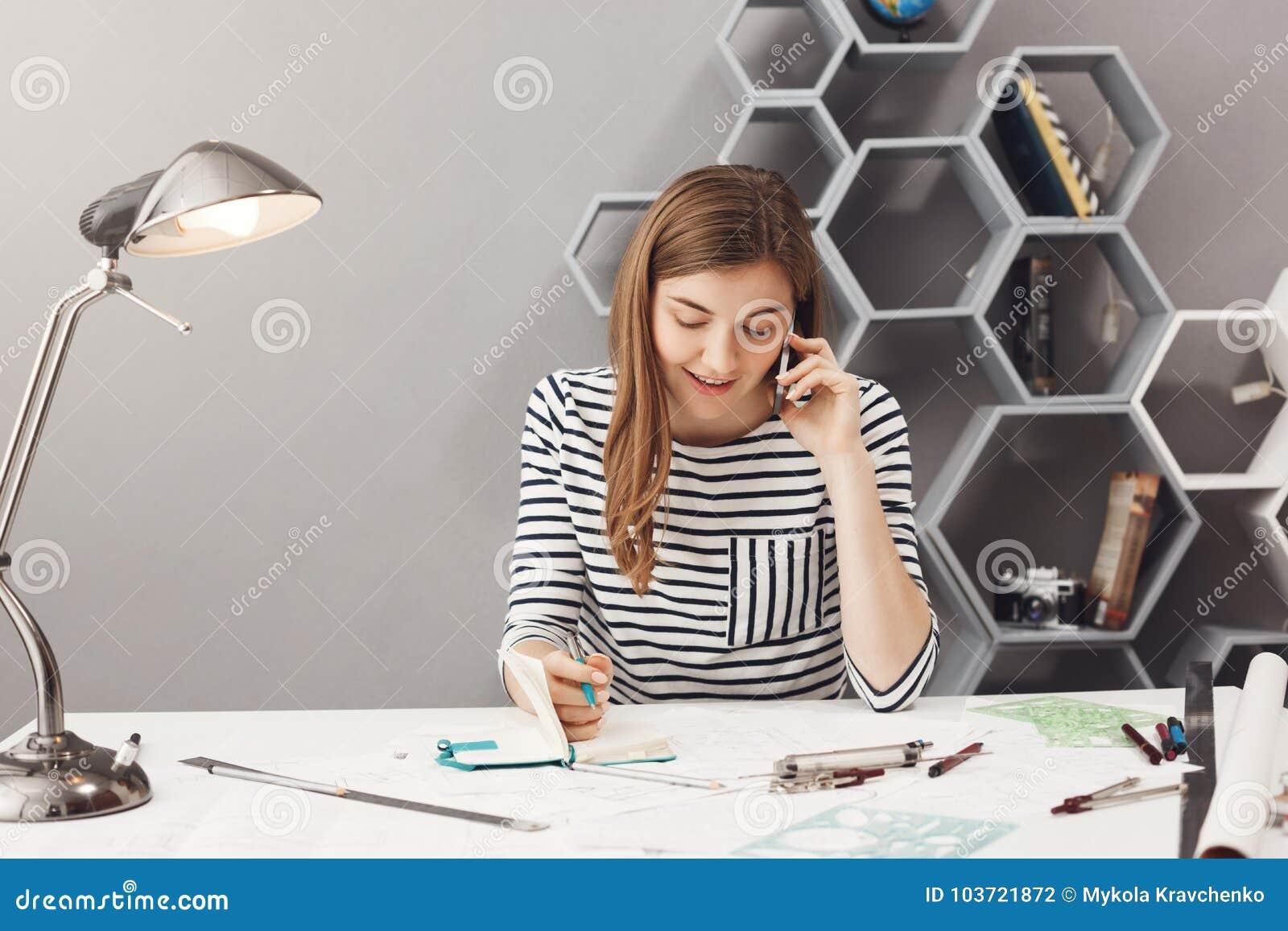 Diseñador joven apuesto del empresario con el pelo oscuro en camisa rayada que habla en el teléfono con la discusión del cliente