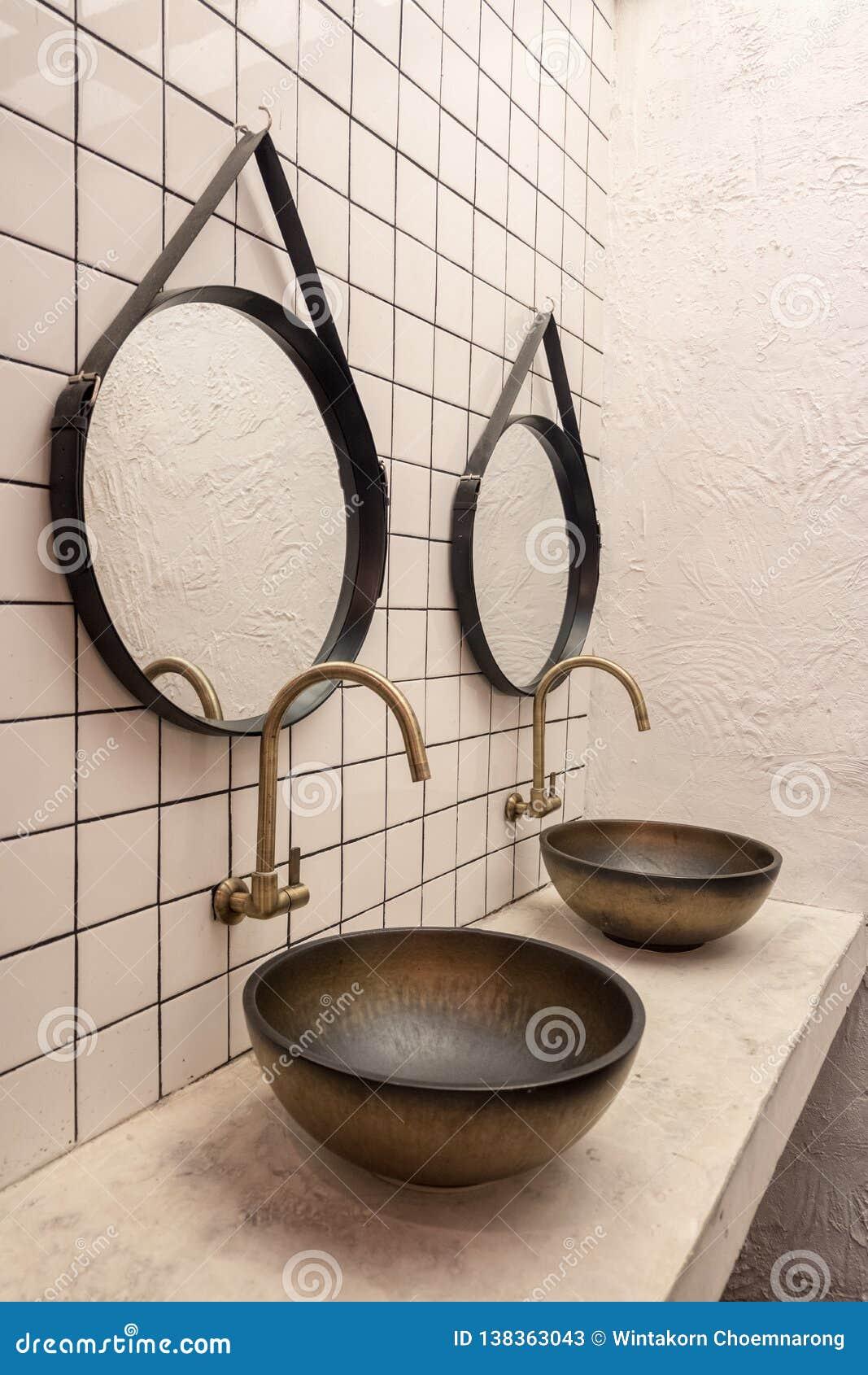 Diseño clásico del cuarto de baño con el golpecito de agua de oro, el fregadero viejo y el espejo retro